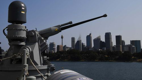 One of the guns aboard the NUSHIP Hobart (III), the first of 3 Hobart Class Guided Missile Destroyers, points out over the city skyline while the ship is moored at Fleet Base East in Sydney.