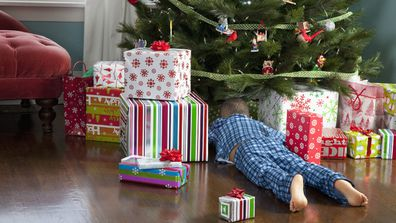 Boy looking under a Christmas tree