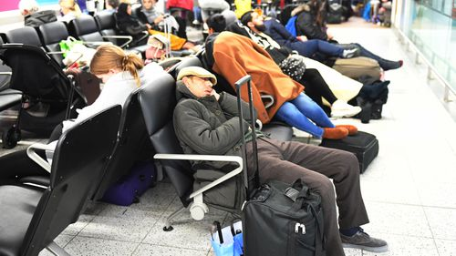 Passengers sleep on chairs inside Gatwick Airport.