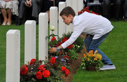A French schoolboy lays a red rose on a soldier's grave during a Headstone Dedication Ceremony for Australian soldiers killed at Fromelles at the cemetery. The nine soldiers will be commemorated during a similar ceremony on July 19, 2018. (AAP)