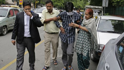 Puneet, second from right, is helped from a New Delhi court by his parents. (Image: AAP)