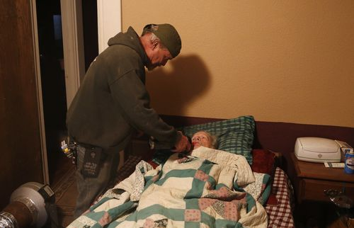 Brad Weldon gives his 89-year-old mother Norma Weldon a drink at their home in Paradise, California.