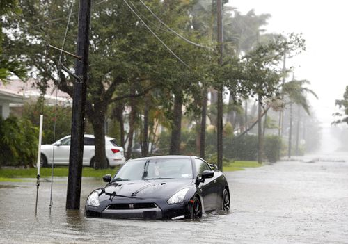 A car is parked on a flooded road as Hurricane Irma passes through Surfside. (AP)