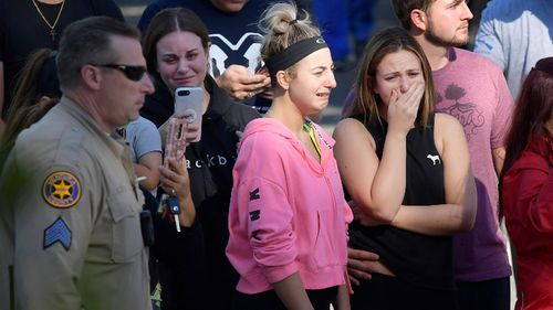 Mourners shed tears after a gunman stormed a country music bar in California.