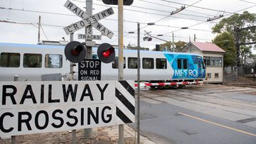 A train crosses the level crossing at Glenferrie Road, in Kooyong, Melbourne.