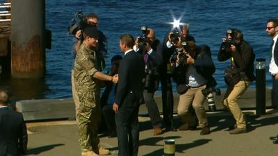 The pair exchange a handshake as a media pack looks on. (9NEWS)