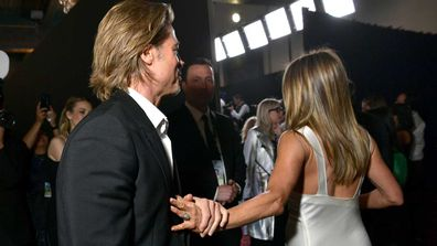 Brad Pitt is photographed grabbing Jennifer Aniston's hand as she walks away at the SAG awards.