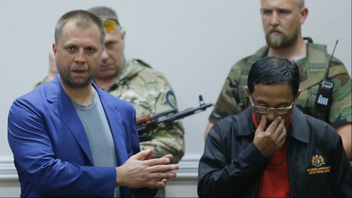 Aleksandr Borodai (L), self proclaimed Prime Minister of the self proclaimed 'Donetsk People's Republic', gestures while speaking at a news conference in which he handed over the two black boxes of the crashed Malaysia Airlines flight MH17 to Colonel Mohamed Sakri (R) of the Malaysian National Security Council. (AAP)