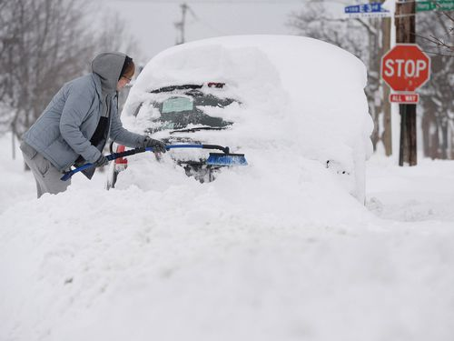 Chelse Volgyes clears snow from her car. (AAP)