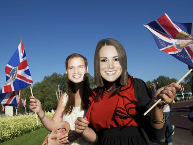 Tourists clad in a mask of Prince William and Kate Middleton pose for a portrait in front of Buckingham Palace days leading up to their royal wedding on April 29, 2011
