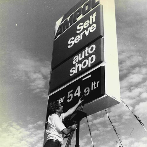 The manager of the Ampol Service Station on Anzac Parade in Sydney's east changes the petrol prices on his sign, in 1987.
