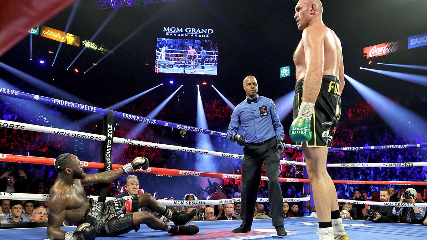 Tyson Fury knocks down Deontay Wilder in the third round during their Heavyweight bout for Wilder's WBC and Fury's lineal heavyweight title