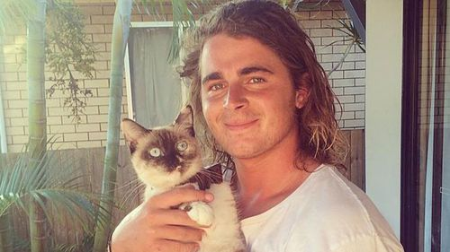 Gold Coast teen Sam Brown with his cat. (supplied)