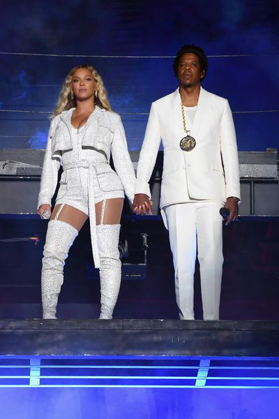 Beyoncé and Jay-Z in coordinating white getups while performing during the 'On The Run' tour.