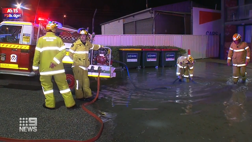 Emergency services work to pump water out of the flooded carpark in Perth.