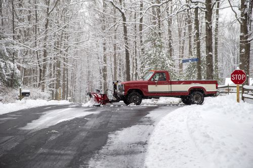 A snow plough operator clears a private road after a winter storm dumped a blanket of snow in Fairfax Station, Virginia.