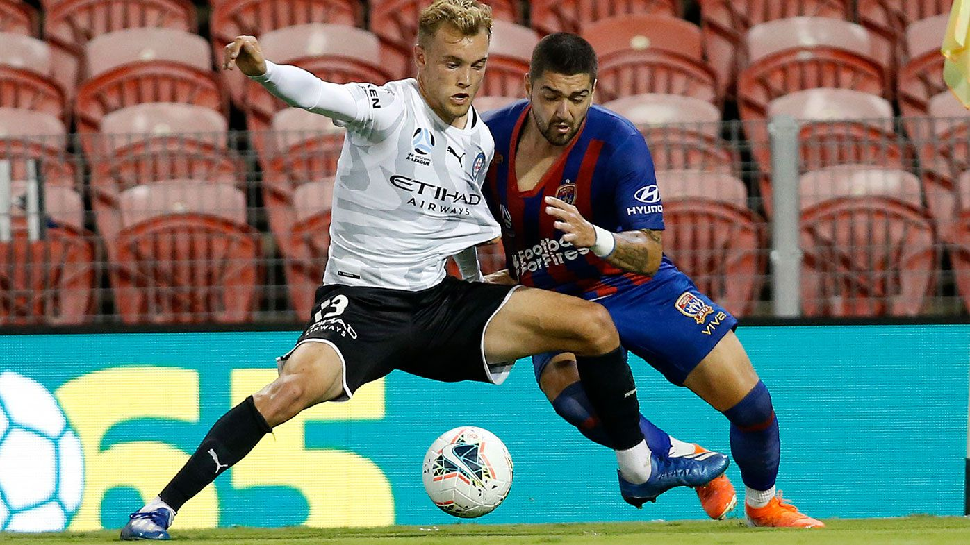 Dimi Petratos of the Newcastle Jets competes for possession with Nathaniel Atkinson of Melbourne City.