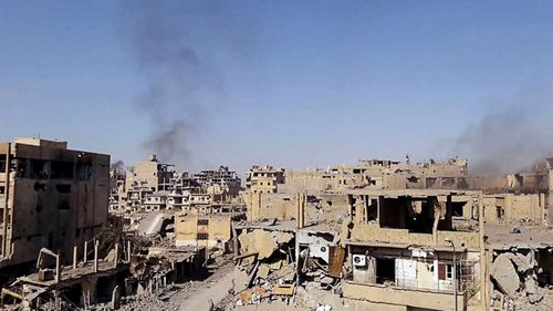 A handout picture made available by Syrian Arab news agency SANA shows damaged buildings in Deir Ezzor city, Syria.