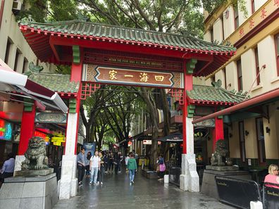 Sydney, Australia - November 5, 2015: People walking passed the gates of Sydney's Chinatown.