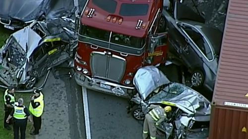 Crumpled and battered cars were crushed between two semi-trailers.