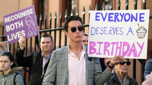 Anti-abortion protesters hold signs during a rally outside the New South Wales Parliament house in Sydney.