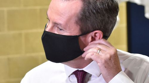WA Premier Mark McGowan takes off his mask.