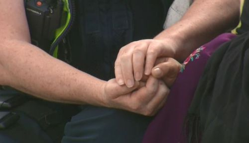 The officer held the mum's hand as she wailed on the street.