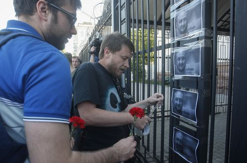 Ukrainian activists place portraits of  Babchenko on a fence of the Russian embassy in Kiev. (AP/AAP)