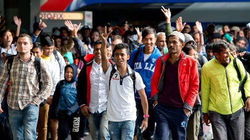 Refugees cheer as they arrive at the main train station in Munich. (AAP)