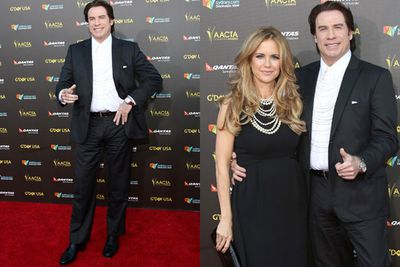 John Travolta poses for the paps alongside wife Kelly Preston in a dapper black suit...what's with the weird shirt though?
