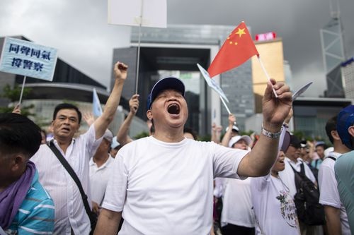 A pro police demonstrator chants slogans and waves a Chinese flag during the rally in support of the police.