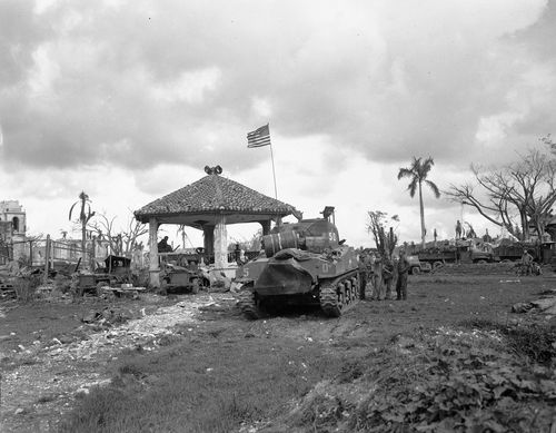 This August 1944 file photo shows an American flag atop the first U.S. tank to lead the push to Agana, capital of Guam. (AAP)