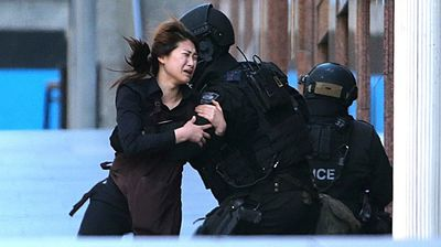 A hostage runs to armed tactical response police officers for safety after she escaped from a cafe under siege at Martin Place. (AAP)