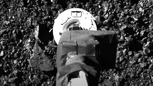 NASA's OSIRIS-REx spacecraft collects a sample.