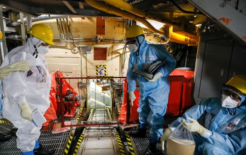 Nuclear experts inspect one of the Fukushima nuclear reactors last year.