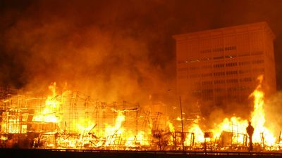 More than 200 Los Angeles firefighters work to control a massive fire as it destroys a seven-story building. (AAP)