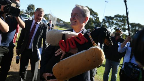 Bill Shorten embraces a sausage dog in Adelaide.