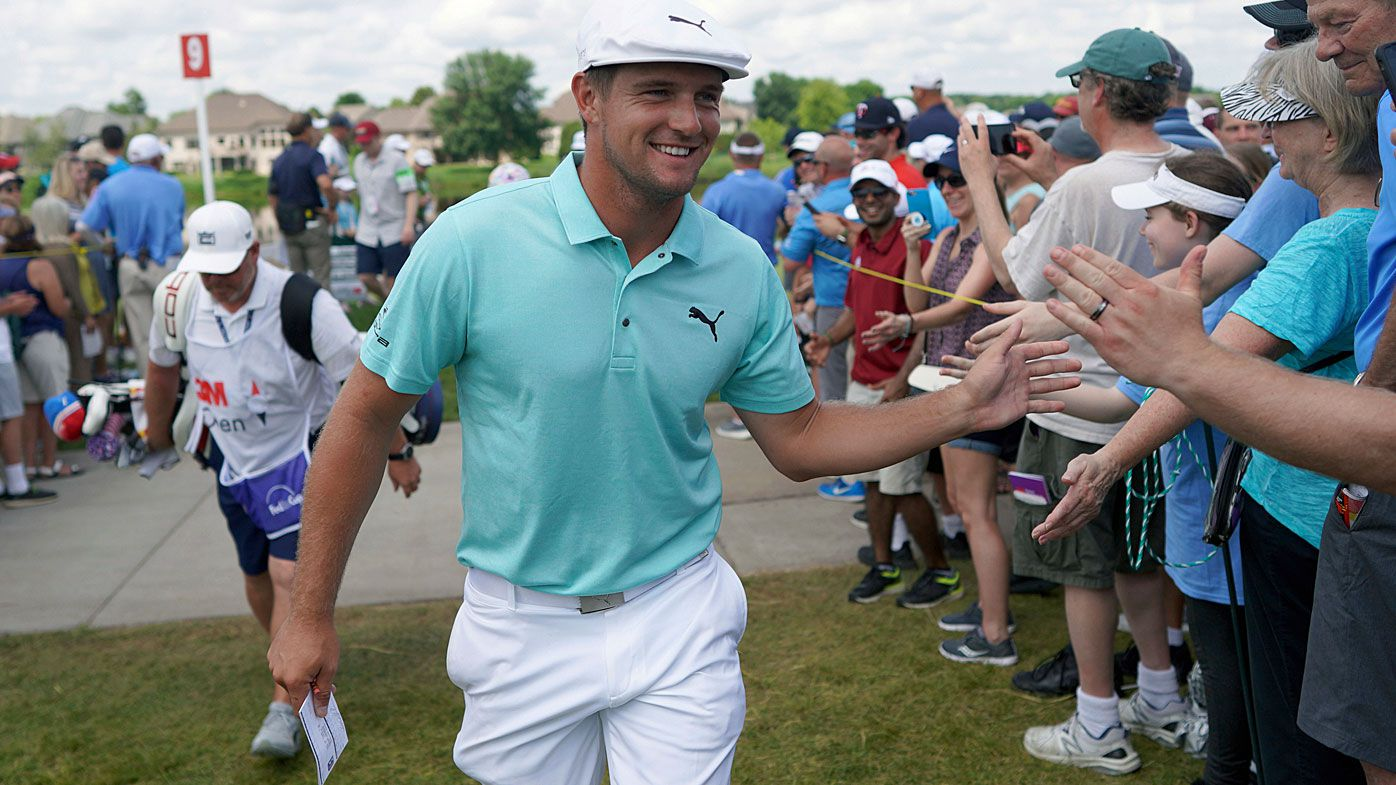 Bryson DeChambeau greets fans as he leaves the ninth hole during the second round of the 3M Open golf tournament