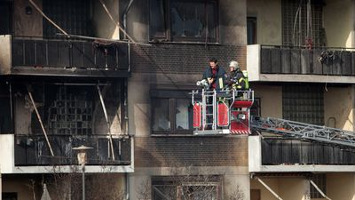 Firefighters stand in a cherry picker in front of a destroyed residential building. (AAP)