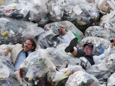 Racegoers jump into a pile of garbage. (Photo: AAP Image/Tracey Nearmy).