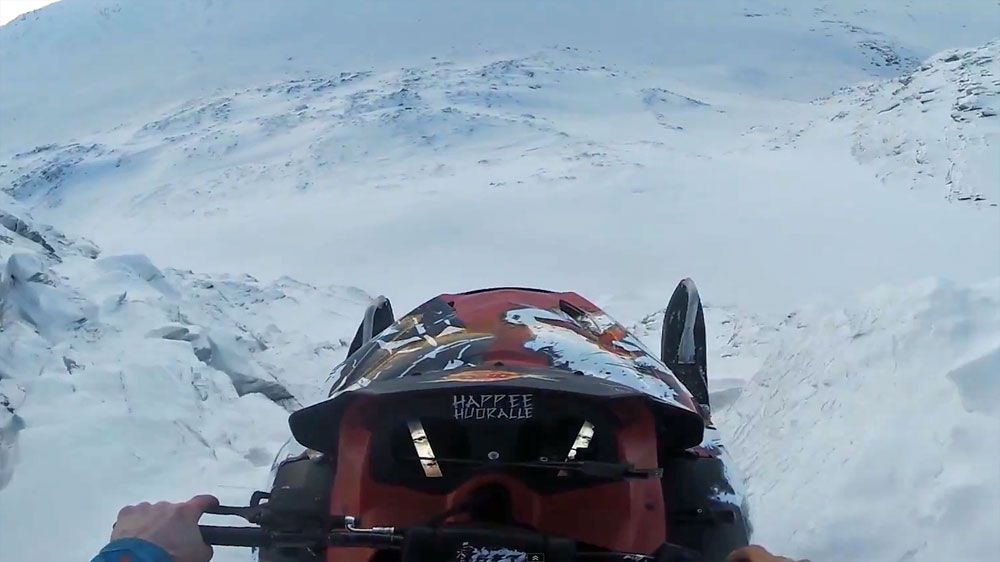 Stuntman soars off cliff on snowmobile