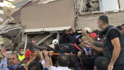 Rescue workers and local people carry a wounded person found in the debris of a collapsed building, in Izmir, Turkey, Friday, Oct. 30, 2020, after a strong earthquake in the Aegean Sea has shaken Turkey and Greece