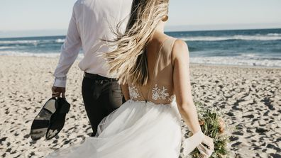 Bride and groom walking on a beach
