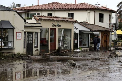 Debris and mud cover the street in front of local area shops after heavy rain brought flash flooding. (AAP)