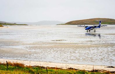 Isle of Barra, Scotland - A small commercial aeroplane, operated by Loganair, on the wet sand of the Outer Hebridean island's unusual beach runway, having just landed.