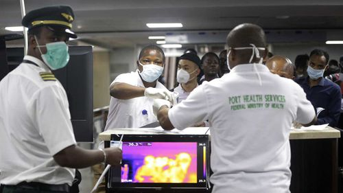 A Nigerian port health official, right, uses a thermometer to screen Ethiopian Airline cabin crews for COVID-19 virus.