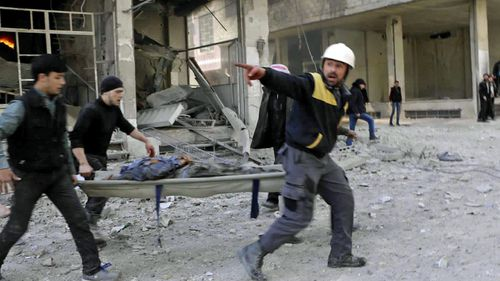 White Helmet workers carry one of the wounded civilians. (AP).