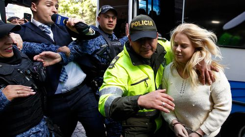 A police officer escorts Australian Cassandra Sainsbury to a court hearing in Bogota, Colombia. (AAP)