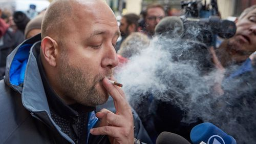 A plume of smoke surrounds a man smoking a joint on the street.