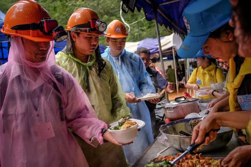 Rescue workers take free lunch from volunteers at the makeshift campsite. Picture: Getty